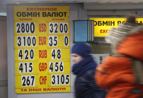 Люди проходят мимо доски, показывающей дневные обменные курсы украинской гривны