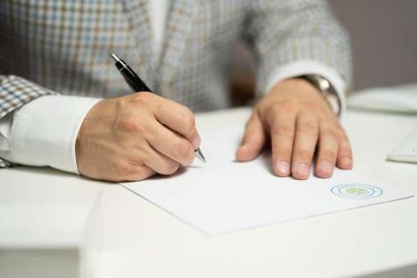Чоловік підписує документ