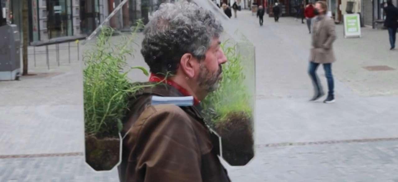 Чоловік носить на голові портативну теплицю, щоб уберегтися від коронавірусу