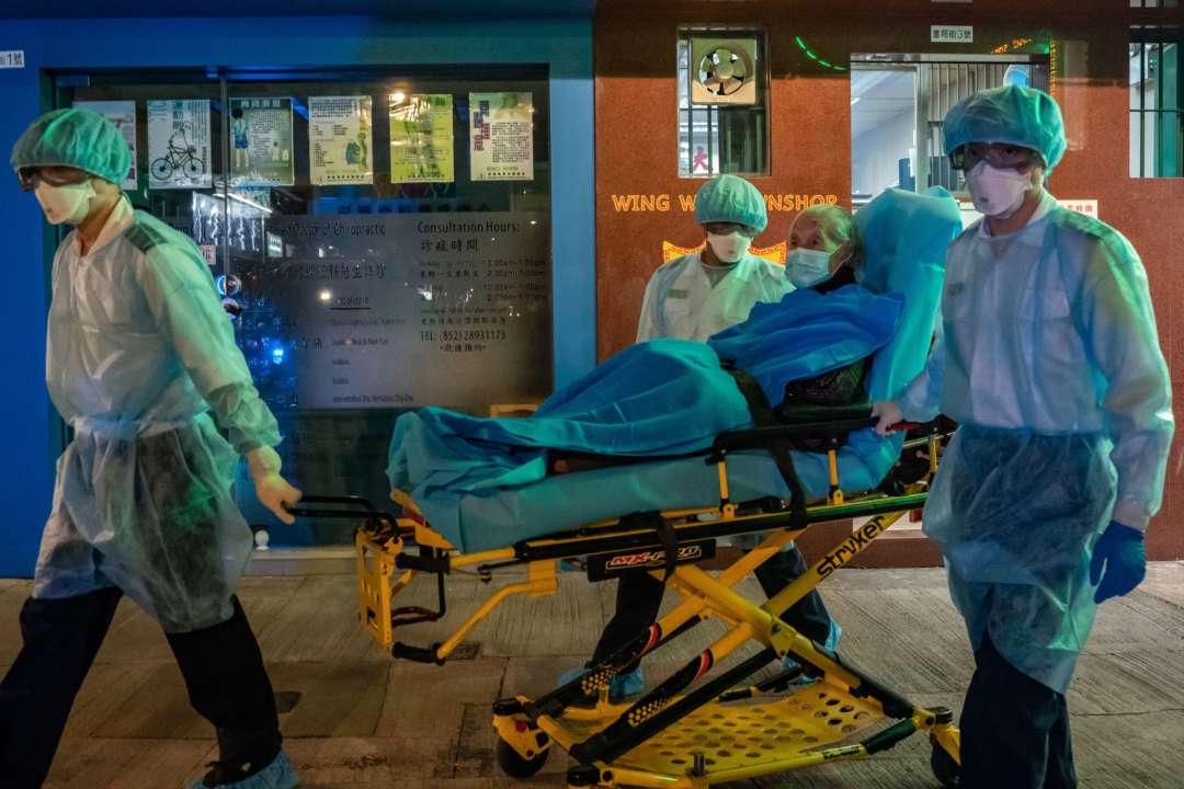 Медработники в средствах индивидуальной защиты несут пациента на носилках